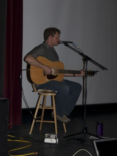 Bozeman-based folk artist Chris Cunningham performs his music for the crowd before Andrew speaks.