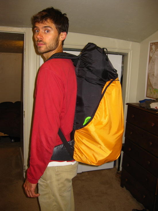 Side view.  Pack has gaiters, raincoat and 2 water bottles in the shove it.